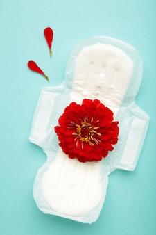 Wit maandverband, hygiënebescherming op een blauwe achtergrond. gynaecologische menstruatiecyclus. een roze bloem ligt op een menstruatiepad. eerste menstruatie. verticale foto