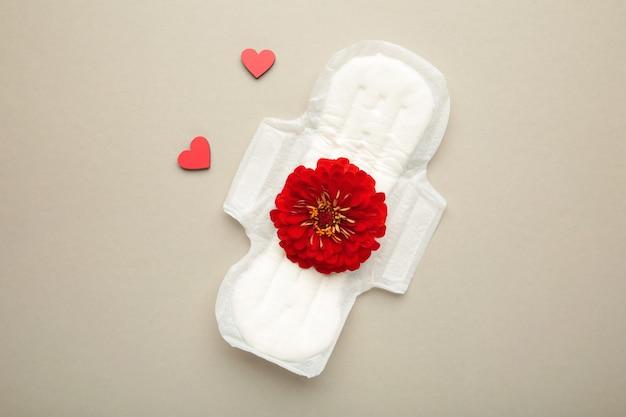 Wit maandverband, hygiënebescherming op een grijze achtergrond. gynaecologische menstruatiecyclus. een roze bloem ligt op een menstruatiepad. eerste menstruatie. verticale foto