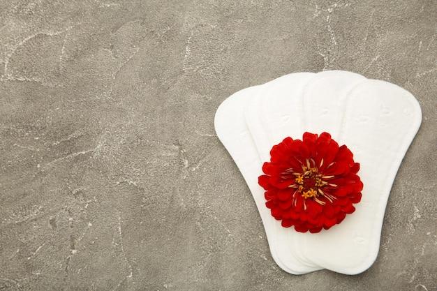 Wit maandverband, hygiënebescherming op een grijze achtergrond. gynaecologische menstruatiecyclus. een roze bloem ligt op een menstruatiepad. eerste menstruatie