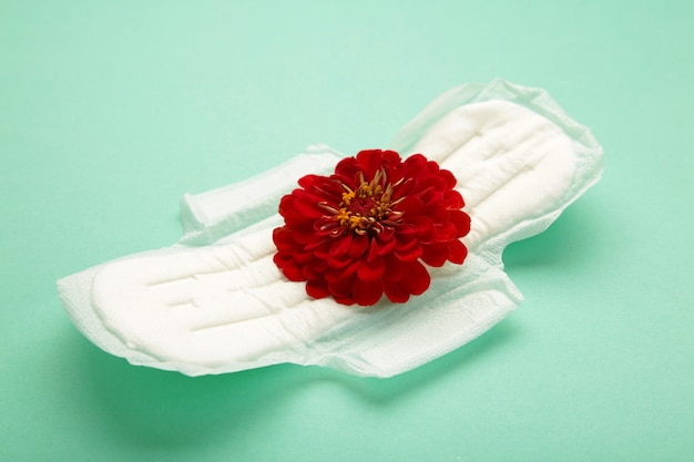 Wit maandverband, hygiënebescherming op een muntachtergrond. gynaecologische menstruatiecyclus. een roze bloem ligt op een menstruatiepad. eerste menstruatie. verticale foto
