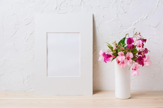 Wit mat frame mockup met roze en paarse bloemboeket