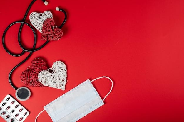 Wit medisch masker met verschillende rode harten en stethoscoop. coronavirus concept