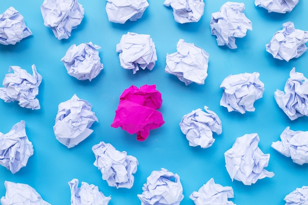 Wit met roze verfrommeld papier ballen op een blauwe achtergrond.