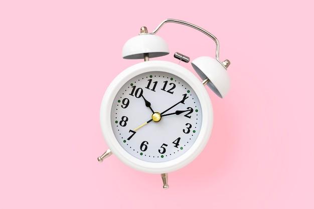 Wit metalen retro wekker met een ronde wijzerplaat op een roze achtergrond, bovenaanzicht. minimalistische vormgeving.