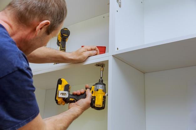 Wit meubilair in moderne keukenschroeven assembleren die schroevedraaier gebruiken
