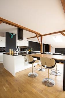 Wit, modern keukeninterieur met barkrukken, zwarte tafel en houten vloer