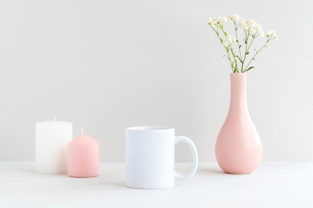 Wit mokmodel met kaarsen, roze vaas en gipskruidtak op een tafel