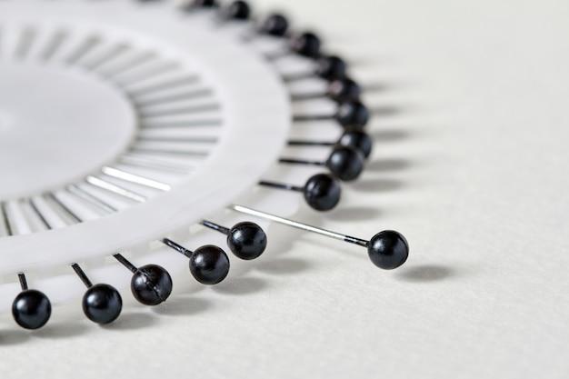 Wit naaldbed met zwarte spelden over witte achtergrond. set naaipinnen met zwarte koppen. close-up, selectieve aandacht