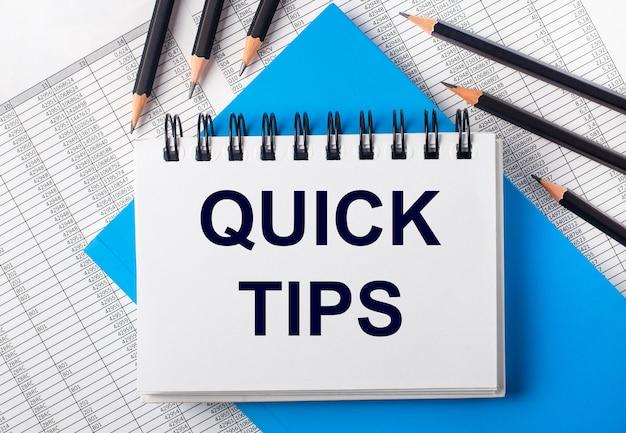 Wit notitieboekje met de tekst quick tips op tafel naast zwarte potloden op een blauwe achtergrond en rapporten. bedrijfsconcept