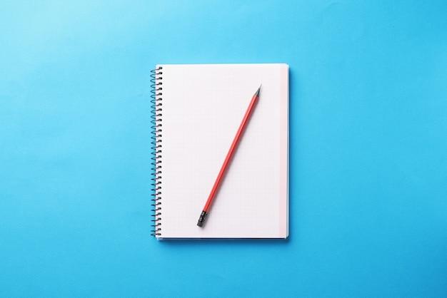 Wit notitieboekje met houten potlood ligt op blauwe achtergrond
