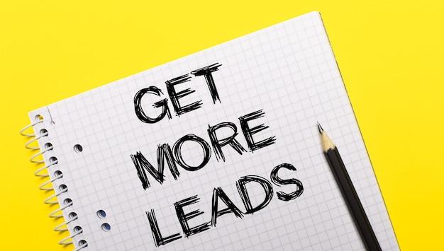 Wit notitieboekje met opschrift get more leads geschreven in zwart potlood op een felgele achtergrond.