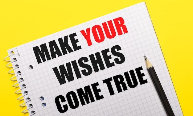 Wit notitieboekje met opschrift make your wishes come true geschreven in zwart potlood op een felgele achtergrond.