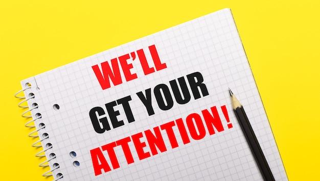 Wit notitieboekje met opschrift we'll get your attention geschreven in zwart potlood op een felgele achtergrond.