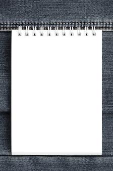 Wit notitieboekje met schone pagina's die op donkerblauwe jeansachtergrond liggen. afbeelding met kopie ruimte