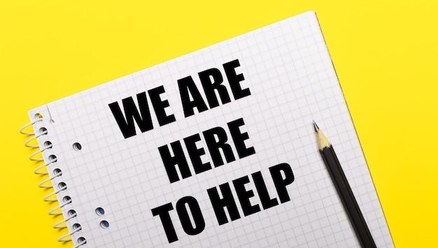 Wit notitieboekje met wij zijn hier om te helpen geschreven in zwart potlood