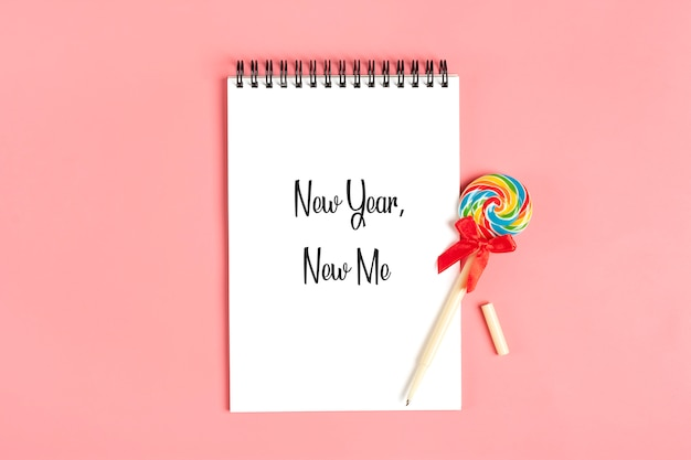 Wit notitieboekje voor nota's, pen - lolly op roze vlakke achtergrond