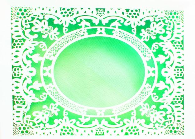Wit opengewerkte kant ovaal papier frame gemaakt in sierlijke luxe stijl op groene achtergrond