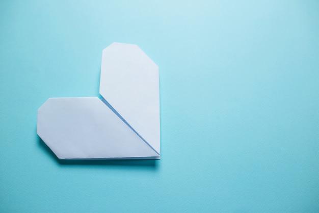 Wit origamihart op blauwe achtergrond. de dagkaart van heilige valentine op blauwe achtergrond.