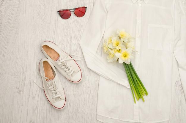 Wit overhemd, bril, sneakers en een boeket narcissen.