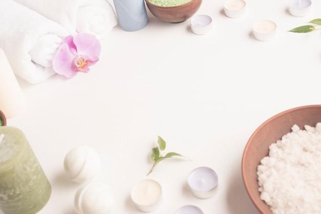 Wit overzees zout, kaarsen, opgerolde handdoek, kuuroordbom op witte achtergrond