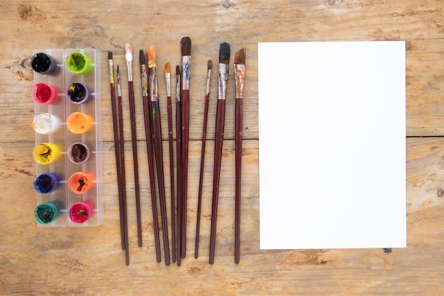 Wit papier in de buurt van gouache en penselen