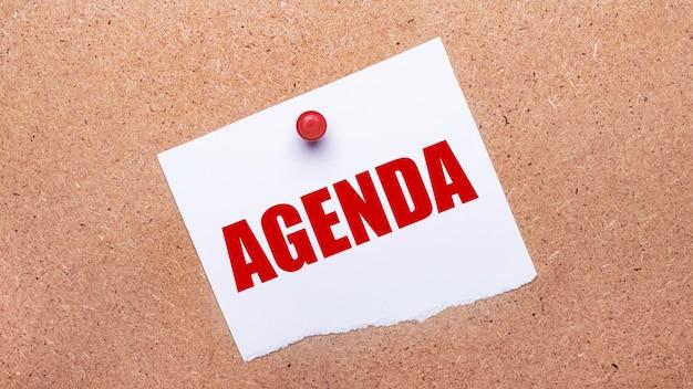 Wit papier met de tekst agenda is met een rode knop op de houten ondergrond bevestigd.