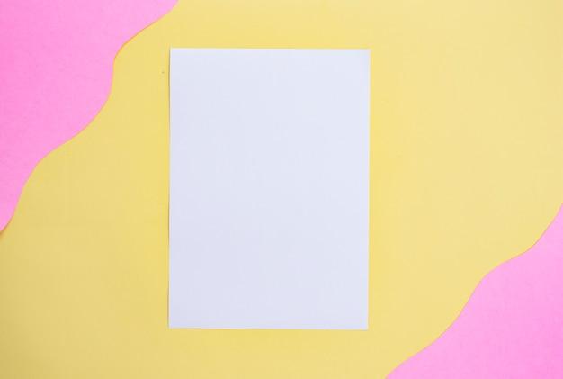 Wit papier op een gele en roze achtergrond. minimalistische stijl