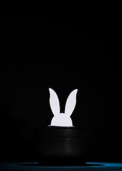 Wit papier uitgehouwen konijnenhoofden in de bovenste zwarte hoed tegen zwarte achtergrond