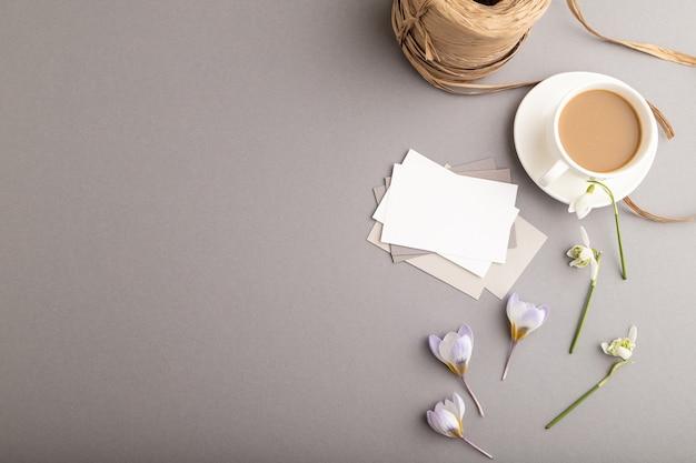 Wit papieren visitekaartje met lentekrokus en galanthusbloemen en kopje koffie
