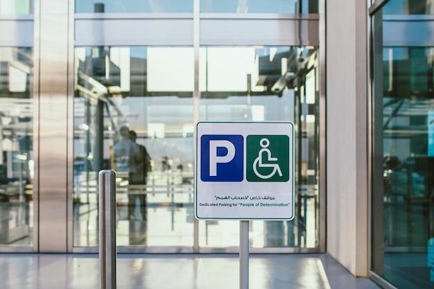 Wit parkeerbord op straat met richting voor mensen en auto's buiten