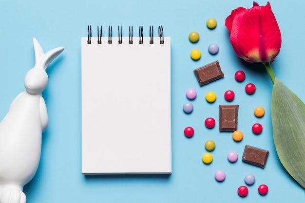 Wit pasen-standbeeld; spiraalvormige blocnote; tulp; edelstenen snoepjes en chocoladestukjes op blauwe achtergrond