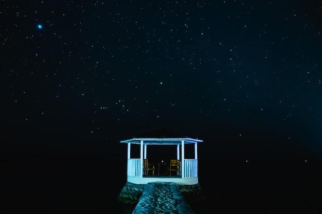 Wit paviljoen met de sterrenhemel in de nacht