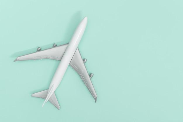 Wit plastic stuk speelgoed vliegtuig dat op blauwe wintertaling wordt geïsoleerd