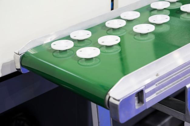 Wit plastic tandwiel gemaakt door injectieproces in transportband