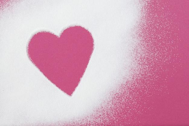 Wit poeder is verspreid over een roze oppervlak, vrije ruimte is in de vorm van een hart. collageen, gezond voedingssupplement.
