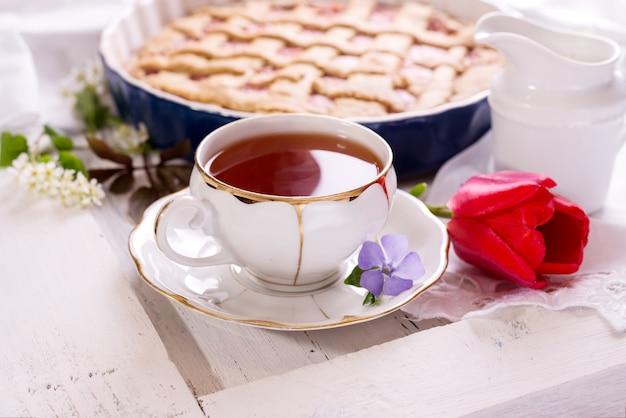 Wit porseleinen kopje thee en versgebakken taart. brits ontbijtstilleven met drank en lekkernijen, rode tulpenbloem en wit tafelkleed.