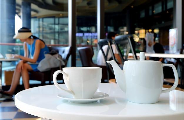 Wit porseleintheestel dat aan de ronde lijst van koffie wordt gediend