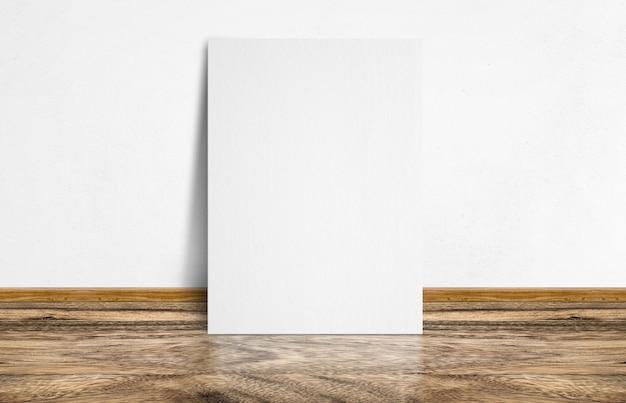 Wit poster die bij rustieke houten vloer en witte muur leunen