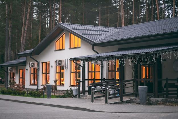 Wit restaurantgebouw met zadeldak in dennenbos, met brandende lichten in grote ramen