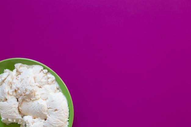 Wit roomijs op groene plaat, magenta achtergrond