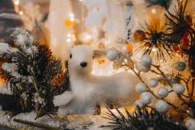 Wit speelgoed fawn en kerstboomtak met zilveren glitter op een feestelijke etalage nieuwjaar
