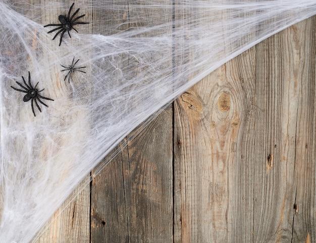 Wit spinneweb met zwarte spinnen op grijze houten van oude raad