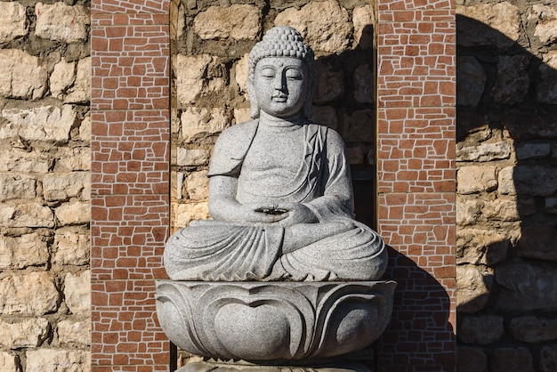 Wit stenen beeld van een boeddha op gemetselde tafel