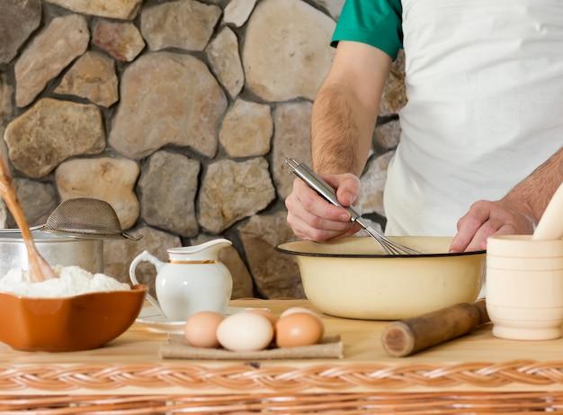 Wit tarwemeel, rauwe kippeneieren en een man koken het deeg