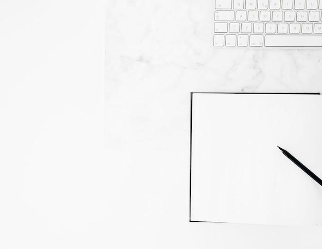 Wit toetsenbord met potlood en notitieboekje op bureau tegen witte achtergrond