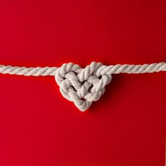 Wit touw in hartvorm knoop op rood oppervlak