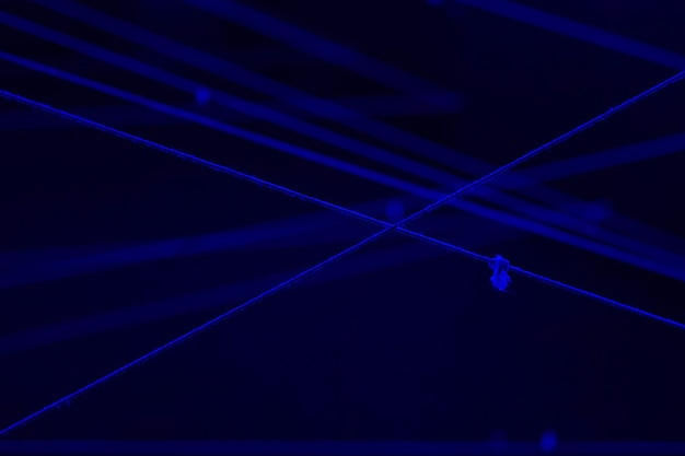 Wit touwkruis in de donkere zwarte lichtruimte voor achtergrond met tekstruimte.