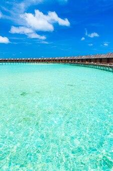 Wit tropisch strand in de maldiven met enkele palmbomen en blauwe lagune