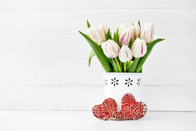 Wit tulpenboeket in witte die vaas met twee rode harten wordt verfraaid. valentijnsdag concept. ruimte kopiëren