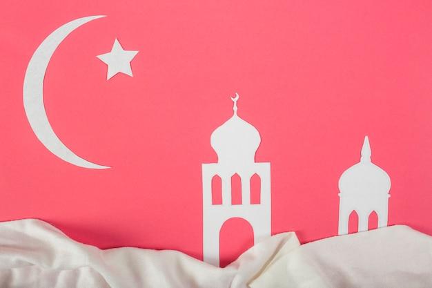 Wit uitgesneden papier met ster; maan en moskee voor ramadan kareem op rode achtergrond